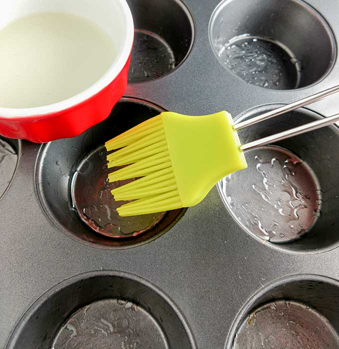 Brushing muffin tin with oil