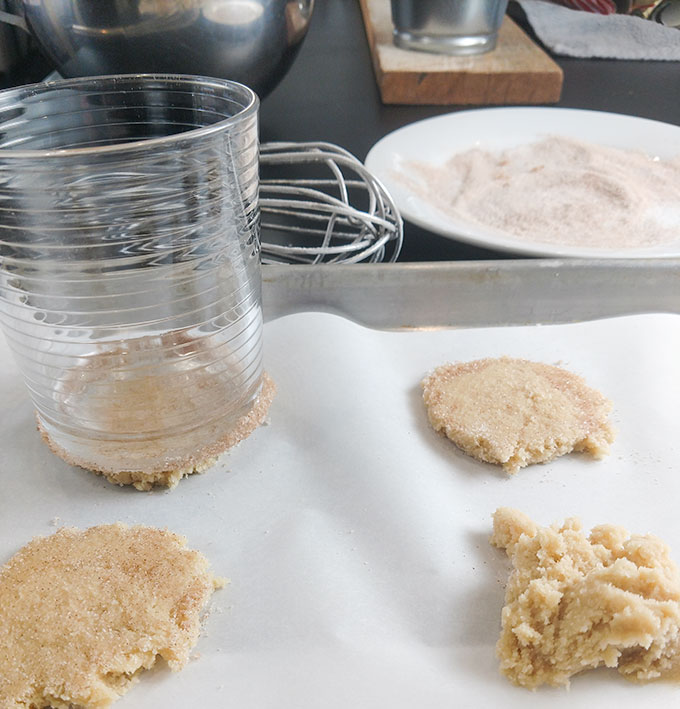 Moms Christmas cookies flattening cookie dough with a glass