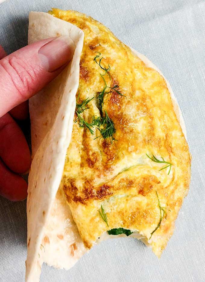 Placing omelette in tortilla for a walking breakfast taco